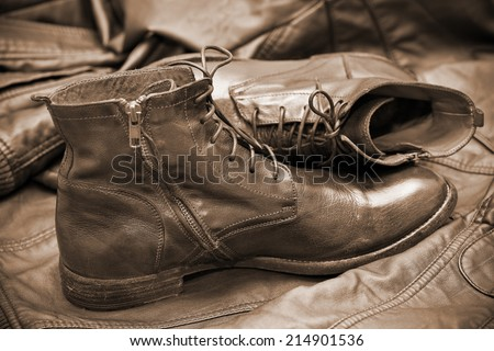 fashionable leather boots and leather jacket. handmade shoes. Autumn and spring shoes. Photo toning in sepia - stock photo