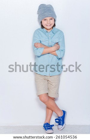 Fashionable little boy. Full length of fashionable little boy in hat keeping arms crossed and looking at camera while standing against white background  - stock photo