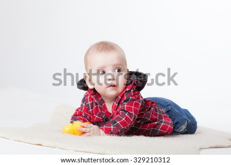 Fashionable little boy, lying on his stomach and smiles