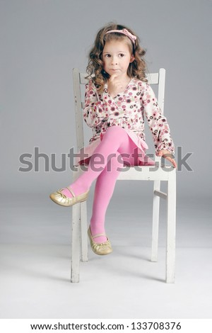 Fashionable little cute girl sitting thoughtful on the white chair, posing, looking away. - stock photo
