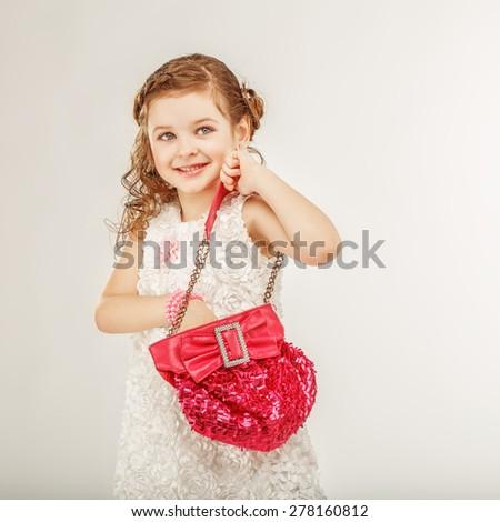Fashionable little girl holding a pink handbag - stock photo