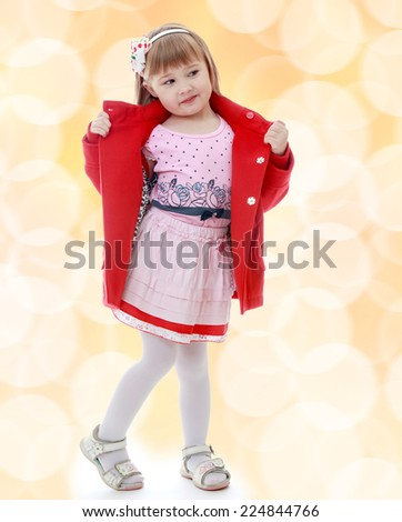 Fashionable little girl in a red coat and a pink dress.Happiness, winter holidays, new year, and childhood.