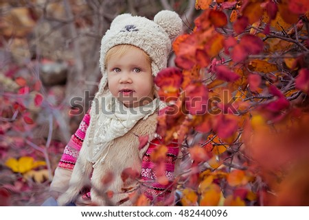 Fashionable little girl in autumn leaves. Fashion funny girl in the autumn forest.  Girl in stylish clothes in autumn park.