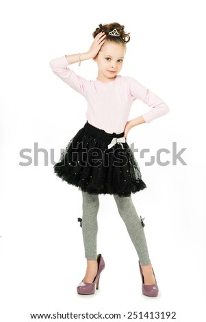Fashionable little girl in big mother's shoes playing a model, posing on a white background - stock photo