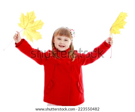 Fashionable little girl in red coat with yellow maple leaves in hands.