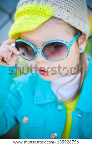 Fashionable little girl outdoors in the park - stock photo