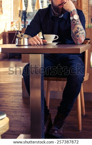 Fashionable male with tattooes sitting at the table in coffee shop with a cup of coffee - stock photo