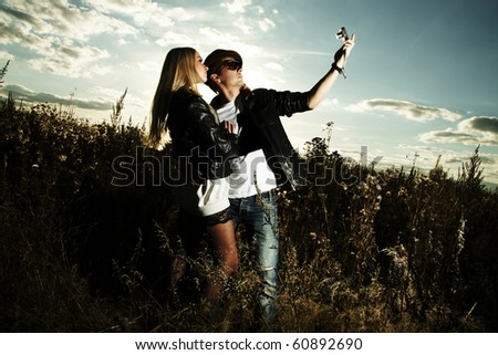 Fashionable man and woman in field of photo shooting on nature - stock photo
