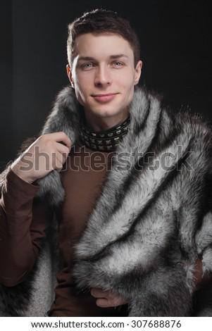 fashionable man in a fur cloak - stock photo