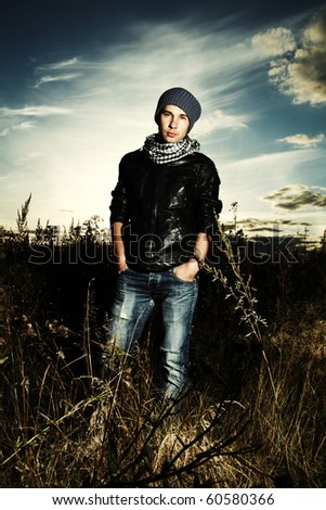 Fashionable man in field of photo shooting on nature - stock photo