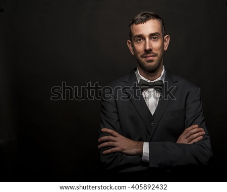 Fashionable man in suite and bow tie over dark background. - stock photo
