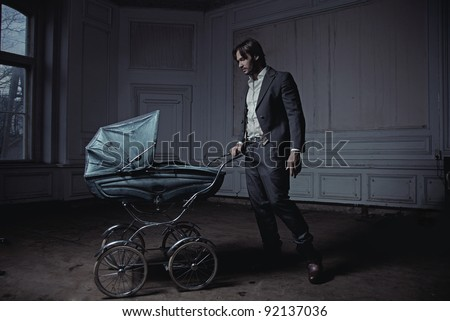 Fashionable man with a perambulator - stock photo