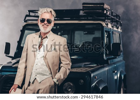 Fashionable Matured Guy in Formal Wear with Sunglasses, Leaning his Back Against his Vintage Vehicle with One Hand in the Pocket. - stock photo