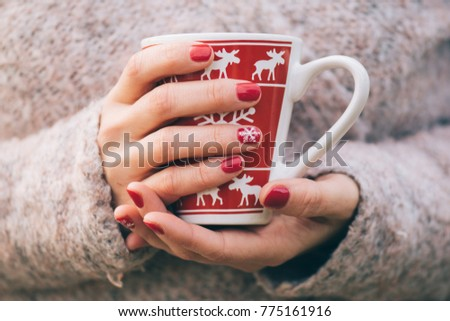 Fashionable nail painting, Christmas style decoration. Mug and female hand.