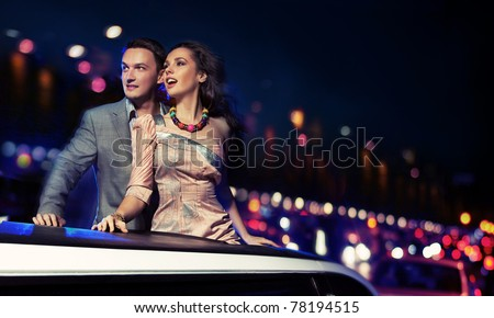 Fashionable pair of elegant people at night city street