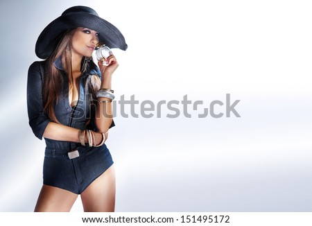 Fashionable photo of beautiful young woman with long hair wearing hat, smelling perfume. A lot of copy space. - stock photo