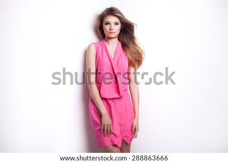Fashionable photo of young beautiful romantic woman with long healthy hair and perfect makeup. Girl wearing pink dress, looking at camera. Studio shoot. Summer, spring style. - stock photo