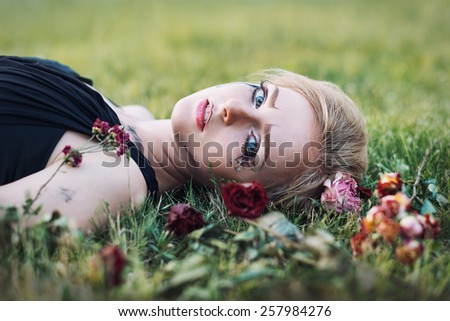 Fashionable portrait of a tearful girl with dry flowers. Retro style. Selective focus - stock photo