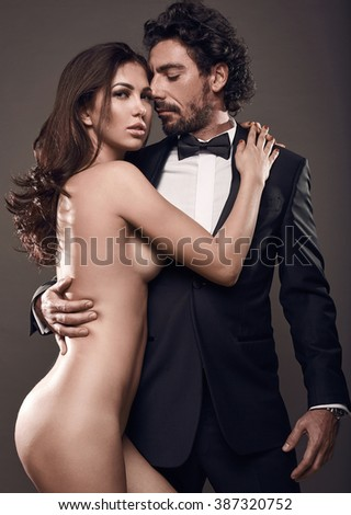 Fashionable portrait of elegant sexy couple in studio. Brutal man in suit hugging a naked woman on dark background - stock photo