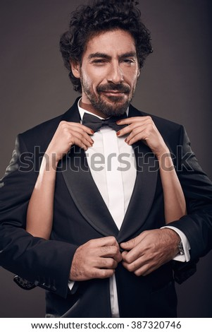 Fashionable portrait of elegant sexy couple in studio. Brutal man in suit with woman's hand touching his face on dark background - stock photo