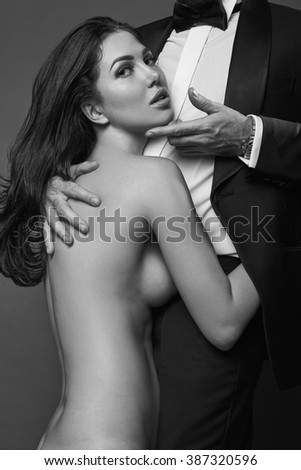 Fashionable portrait of elegant sexy couple in studio. Naked beautiful woman hugging a brutal man in suit on dark background. Grayscale - stock photo