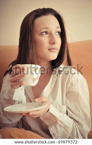Fashionable portrait of young pretty domestic woman wearing shirt drinking her coffee in the morning with natural light - stock photo