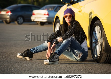 Fashionable punk woman sitting on the car parking - stock photo