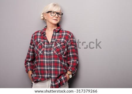 Fashionable senior woman with grey hair posing in studio. Casual look. - stock photo