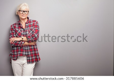 Fashionable senior woman with grey hair posing in studio, looking at camera. Casual look.
