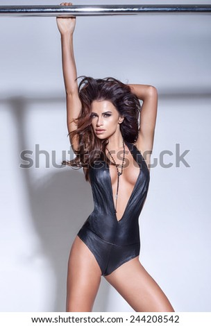 Fashionable sexy brunette woman posing in studio, looking at camera. - stock photo