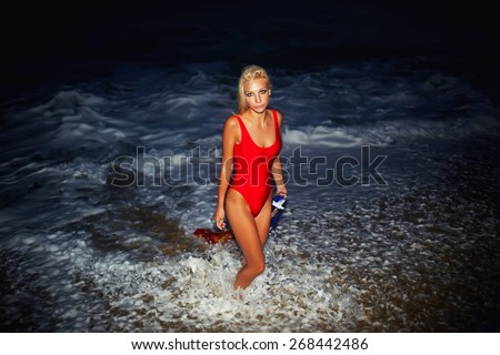 Fashionable sexy model posing on the ocean beach at night holding Catalonia flag, blond hair caucasian girl with beautiful figure dressed in red swimsuit at sea coastline - stock photo
