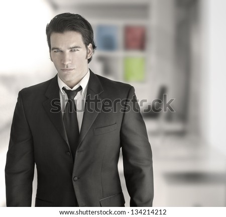 Fashionable sexy young businessman in modern setting - stock photo