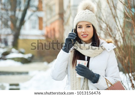 fashionable smiling woman talking on the phone. winter stylization