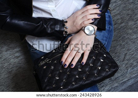 Fashionable stylish young woman in jeans and black leather jacket with black handbag and silver watch - stock photo
