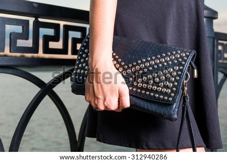 Fashionable stylish young woman with black handbag is posing outdoors near fence. Small fashion black clutch is covered with rivets. Fashion luxury leather hand bag - stock photo