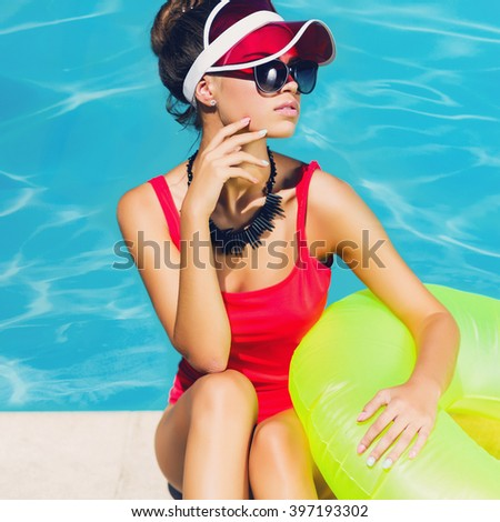 Fashionable  tan woman in stylish red one-piece swimsuit  sitting on steps near pool  with  rubber ring, Outdoor fashion portrait of pretty lady enjoying  summertime  on her vacation. - stock photo
