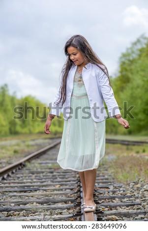fashionable thai girl balancing on railroad track - stock photo