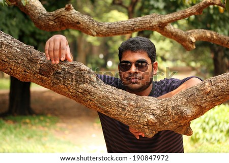 fashionable trendy modern indian traveller at a park with trendy sunglasses and looking cool & casual with summer dressing