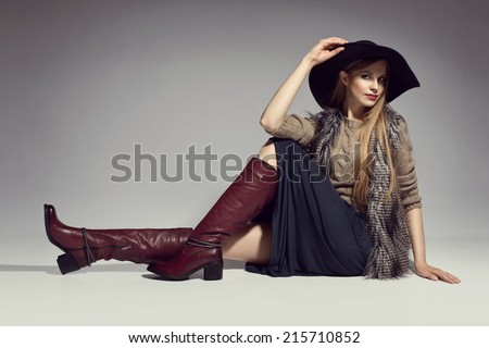 Fashionable woman in a hat, boots and autumn clothes, posing in studio  - stock photo