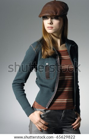 fashionable woman in a hat posing in light background - stock photo