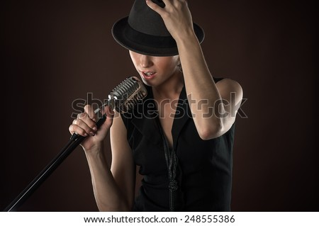 fashionable woman in a hat with a retro microphone - stock photo