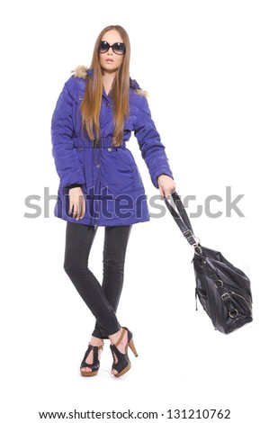 fashionable woman in sunglasses with handbag posing