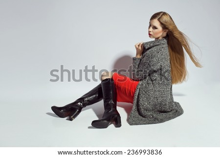 Fashionable woman in sweater, boots and autumn clothes, posing in studio - stock photo