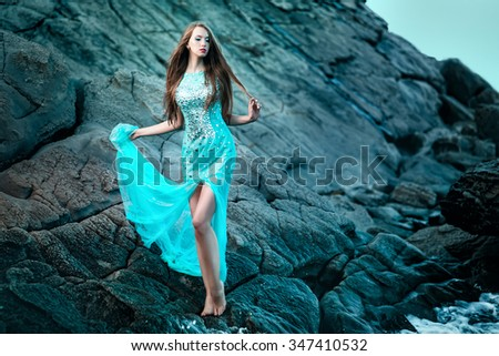Fashionable woman posing on a beach with rocks in a long dress