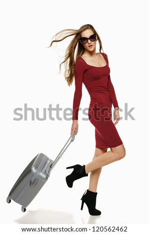 Fashionable woman running with suitcase, over white background - stock photo