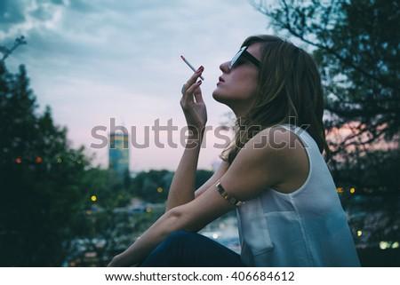 Fashionable woman smoking cigarette outdoors. - stock photo