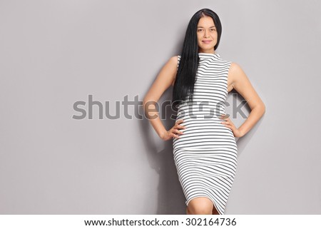 Fashionable woman wearing a striped black and white dress and leaning against a gray wall - stock photo
