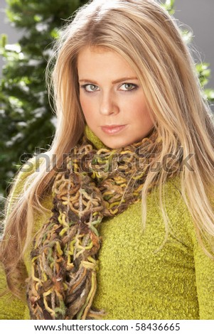 Fashionable Woman Wearing Knitwear And Scarf In Studio In Front Of Christmas Tree - stock photo