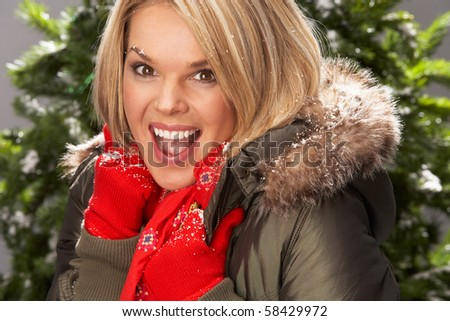 Fashionable Woman Wearing Parka Coat And Scarf In Studio In Front Of Christmas Tree - stock photo