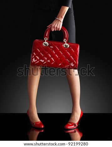 fashionable woman with a red purse, only legs